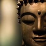A close up of a bronze Buddah's face.